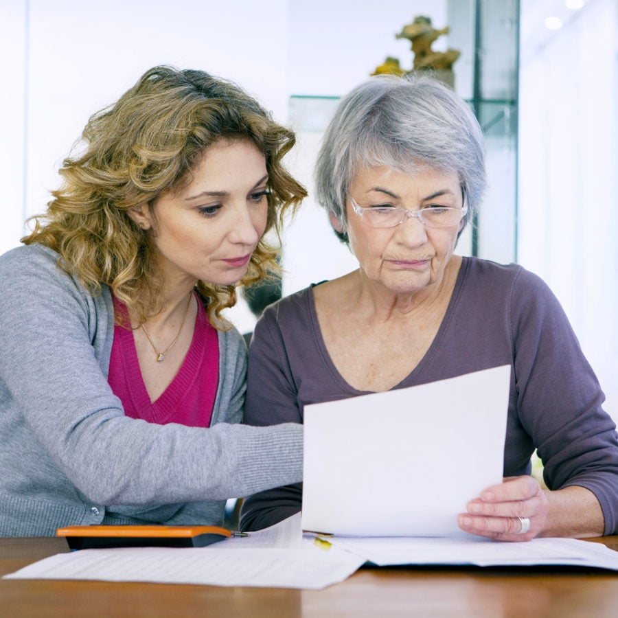 Cancer Support France can help you - Woman helping elderly lady with forms